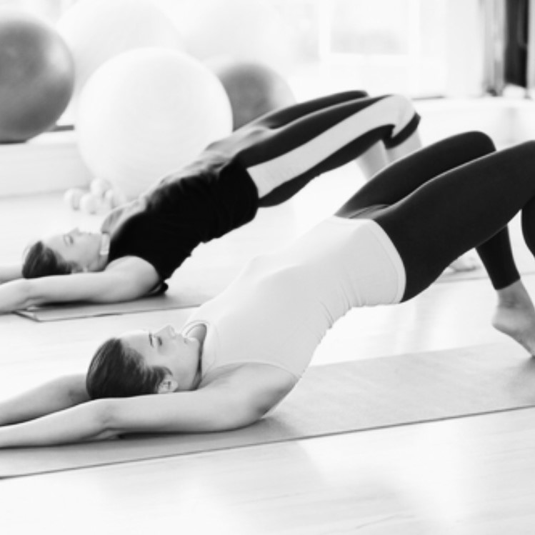 Black and white photo of two people doing mat pilates